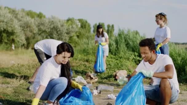 Konzept der Recycling-Müll Gruppe von jungen Freiwilligen multiethnisch sammeln den Müll vom Strand und sammeln auf den blauen Plastiktüten