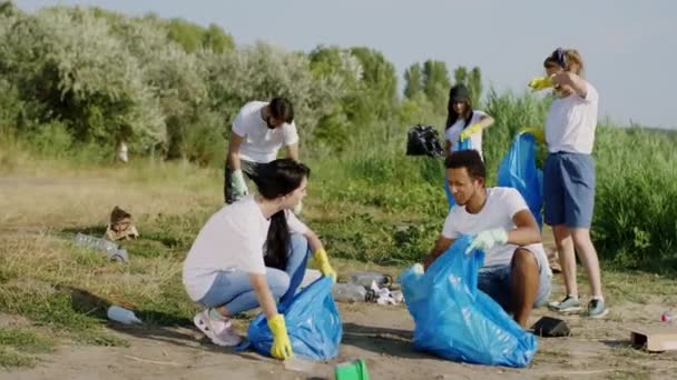 Gruppe multiethnischer Freiwilliger an einem sonnigen Tag beim Aufräumen des Mülls am Strand, den sie auf den blauen Plastiktüten sammeln