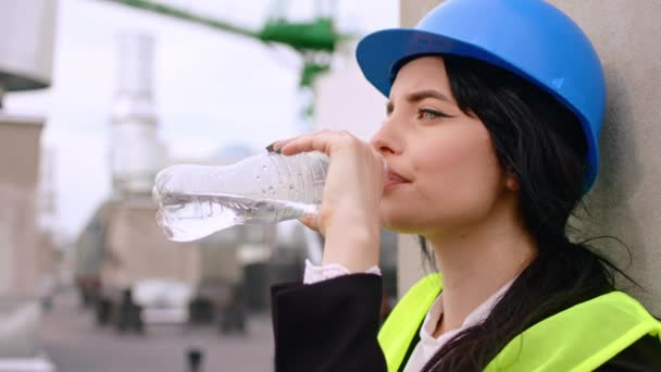 Portrait of a young woman very thirsty drink some water on the construction site she wearing a safety helmet