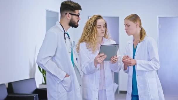 Charismatische reife Ärztin und zwei Krankenschwestern auf dem Krankenhausflur, die eine Diagnose des Patienten vom digitalen Tablet analysieren