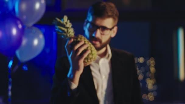 Karizmatikus fiatalember közel a kamerához a partin érezd jól magad egy ananásszal, amit koncentráltan tart, és egyenesen a kamerába néz. 4k