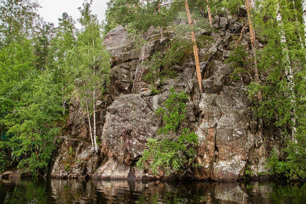 primal stony shore of a calm lake in Karelia
