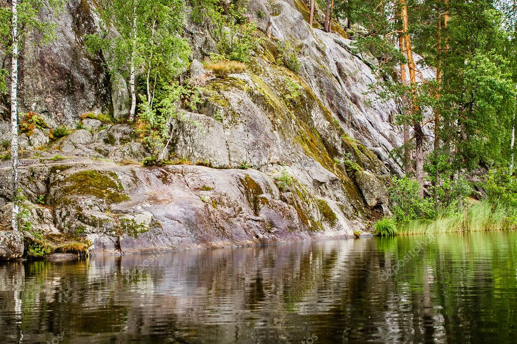 primal rocky shore of a calm lake in Karelia