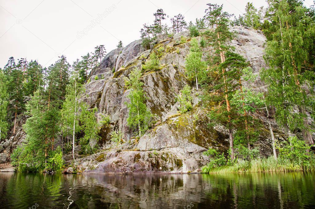 primeval rocky mountain on the shore of a calm lake