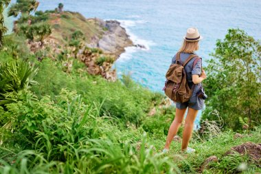 Young traveling woman with camera and rucksack enjoying sea view.
