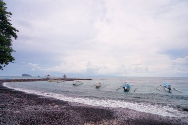 Beutiful balinese seascape with beach, traditional fishing boats and cloudy sky.