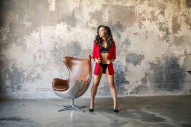 Petite caucasian brunette girl posing half-dressed in red jacket with armchair before grungy wall