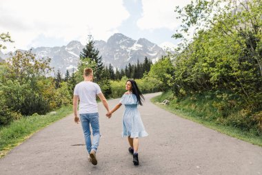 Rear view of young couple walking by mountain path