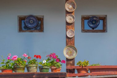 Romanian traditional ceramic plates from Horezu area, Romania, placed ornamentally on rustic house windows and on a wooden pole.
