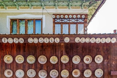 HOREZU-OLARI, ROMANIA - JULY 23, 2020: Romanian traditional ceramic plates placed ornamentally on a rustic wooden wall at house. Artists names on the plates.