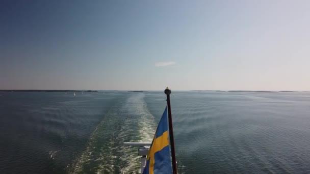 Švédská vlajka na zádi lodi. Plavba po Baltském moři. Finský záliv. Pohled na probuzení z trajektu. Praporek ve větru. Léto, bezmračná obloha a obzor. Pohyb kamery shora dolů.
