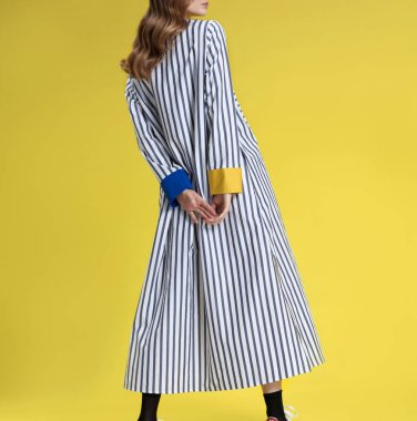 Young girl with long blonde hair in fashionable clothes, black and white with colored inserts long striped shirt dress posing on bright yellow background, studio shot