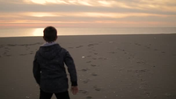 The boy walks along the beach at sunset.