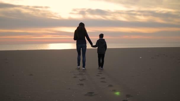 Maminka a její syn jdou podél pobřeží při západu slunce.