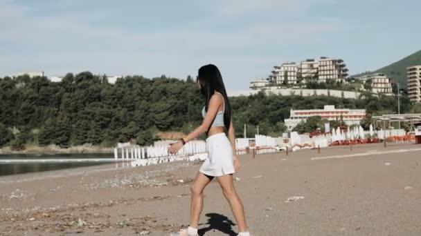 Beautiful girl in sunglasses walks on the beach