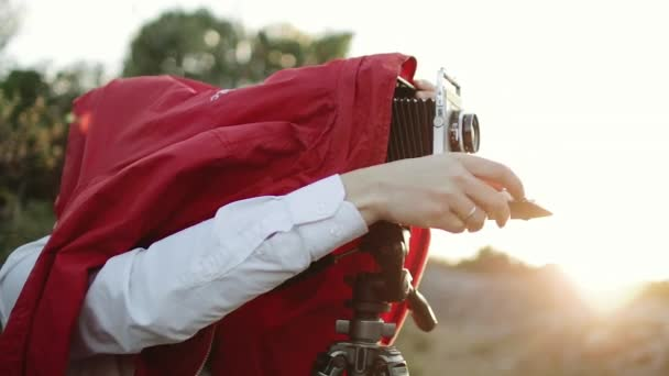 The photographer works with the old camera. Cover with a cape and take pictures.