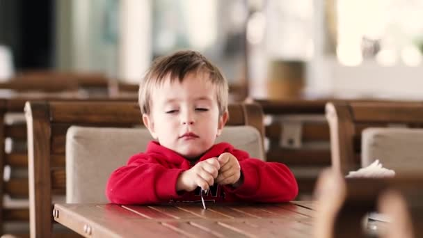 Little boy sits at the table and holds a big spoon