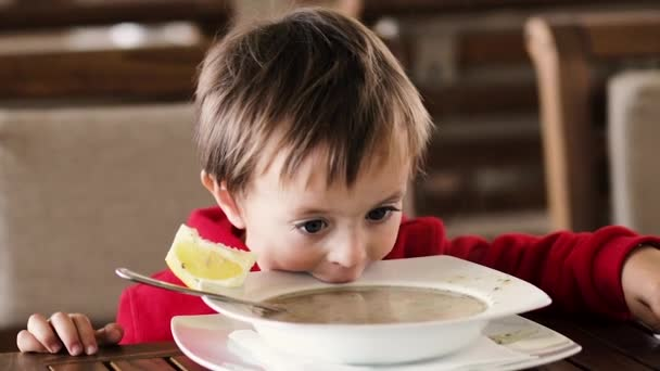 Little boy eats soup and bread at the table