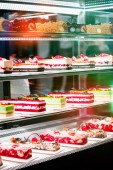 Fotografie Showcase with different types of cakes in pastry shop