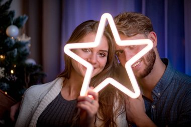 Cheerful couple sitting next to christmas tree and holding glowing LED star in dark cozy room at xmas eve
