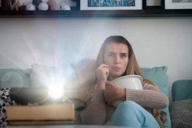 Woman on sofa watching movie using digital LCD video projector, home theater