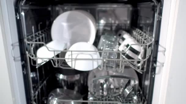 Close-up view of clean white dishes in the dishwasher