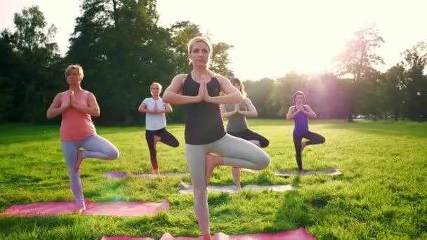 Smíšená skupina lidí praktikující jóju venku v parku během západu slunce