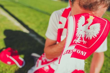 Crying Polish Soccer Fan. Lost Match Theme. Caucasian Football Fan Covering His Face by National Team Red and White Scarf with Polish Emblems.