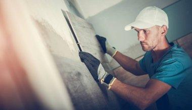 Bathroom Tiles Replacing. Caucasian Worker in His 30s Installing Brand New Ceramic Tiles.