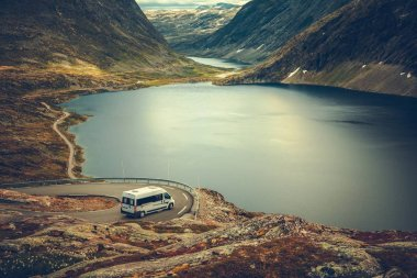 RV Camper Scenic Road Trip. Raw Norwegian Landscape and the Camper Van Recreational Vehicle on the Winding Mountain Road near Famous Village of Geiranger.