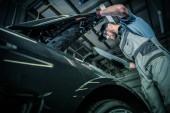 Fotografia Manutenzione auto moderne. Pre veicolo allinterno del servizio di Auto di proprietà. Meccanico di automobile indoeuropeo nel suo 30s dare occhiata sotto il cofano. Tema automobilistico