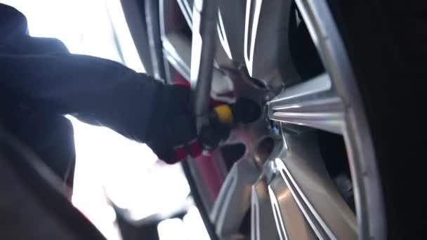 Připojení pneumatiky po vyvážení. Detailní záběry auto služby