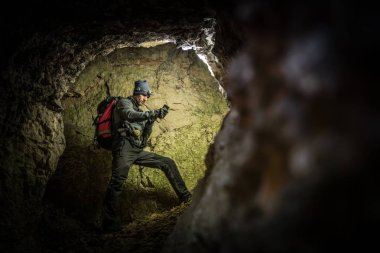 Deep Cave Exploration by Men with Flashlights and Backpack. Caucasian Caver in the Grotto.