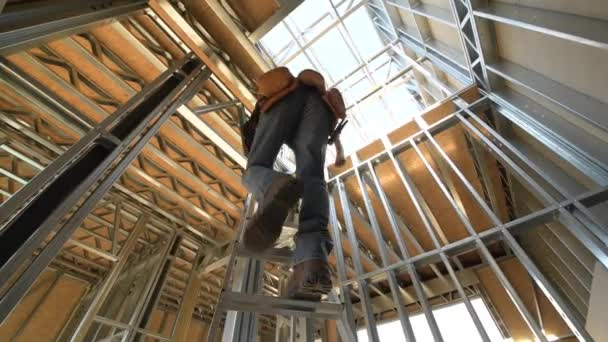 Construction Site. Caucasian Steel Frame House Contractor Builder on a Ladder.