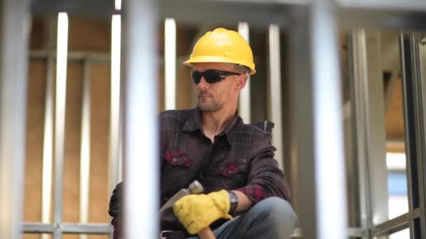 Caucasian Builder with Hammer and the Construction Site.