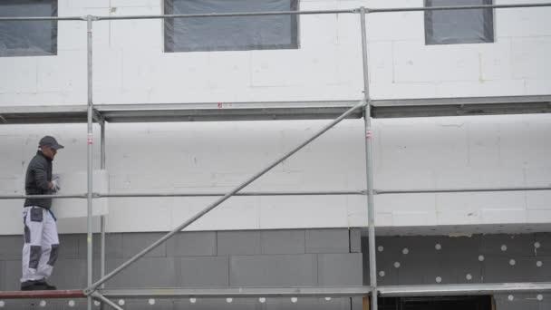 Kaukasische Arbeiter auf einem Gerüst arbeiten mit externen Gebäudedämmung.
