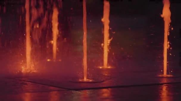 Zeitlupe des kleinen bunten Springbrunnens in der Nacht