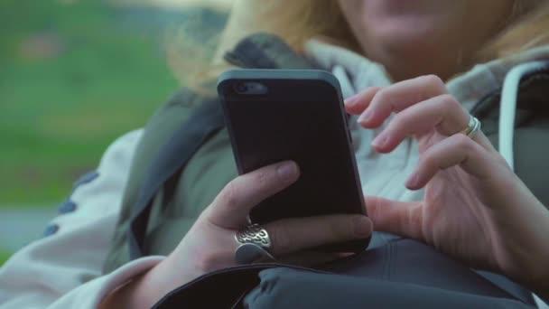 Žena s Smartphone kontrola sociální média při posezení venku