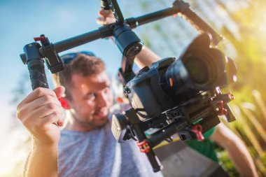DSLR Digital Video Camera on a Gimbal. Caucasian Cameraman with Motion Picture Camera Installed on Professional Stabilizator.