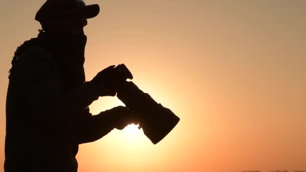 Safari Fotografo allaperto al tramonto. Silhouette of Men Mantenimento della fotocamera digitale in mano con grande teleobiettivo lente per i migliori primi nella fauna selvatica. Metraggio slow Motion