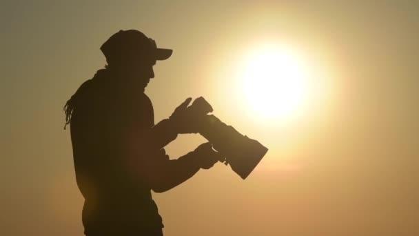 Fotografo allaperto attrezzata con grande teleobiettivo nella posizione remota durante il tramonto scenico.