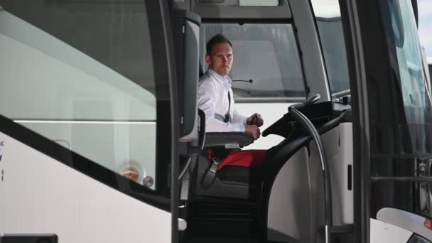 Caucasian Male Bus Driver Sitting In Cabin Putting Sun Glasses Away Looking At Entrance Of Vehicle And Talking To Passenger Standing Outside.