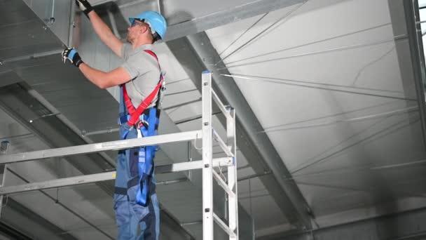 Instalace klimatizačního systému na stropě komerčních budov manuálním pracovníkem.