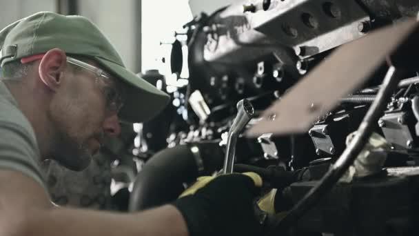 Oprava Servis Muž Technik Práce na sběrnici Motor v mechanické garáži pomocí klíčů k utažení šroubů mechanismu.