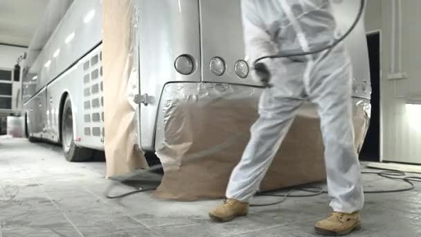 Karosszéria munkás teljes védőfelszerelés ellenőrzése Új spray festés munka a nagy kereskedelmi busz.