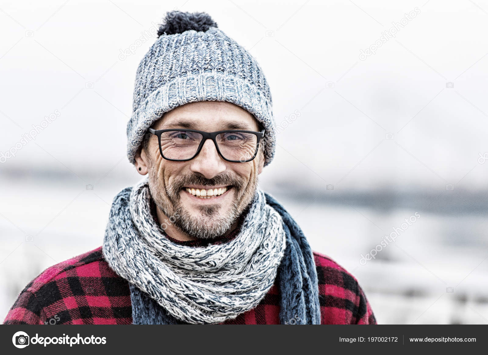 Portrét městského člověka v zimě pletené oblečení. Portrét muže v brýlích a  pletená bílo modrá šála a čepice. Portrét šťastný člověk. ef034604ab