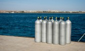 Group cylinders with helium on dock. ten white cylinders for divers on sea dock. oxygen tanks for divers on pier. Blue sea water and steel cylinders. Closeup of ten divers aluminum balloon on pier.