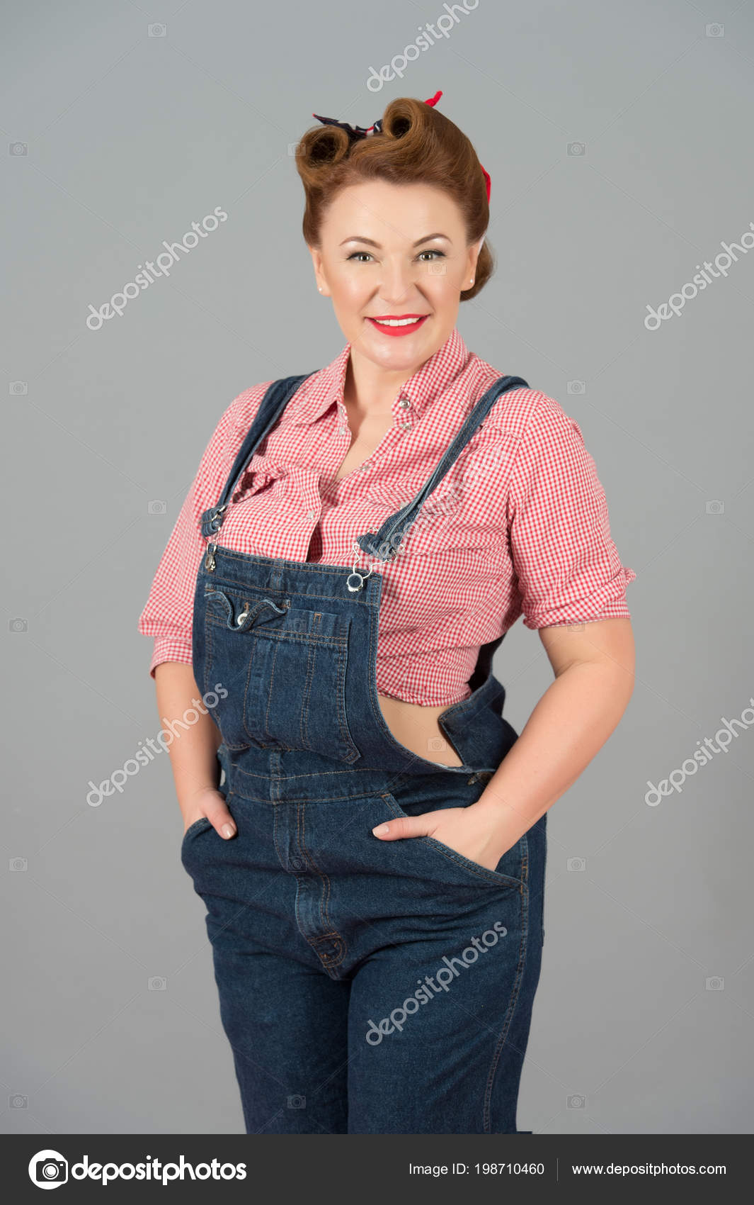 0a1d51ded705a9 Brünette hübsche Frau im Pin-up-Stil und Denim auf grauem Hintergrund.  Konzept der Jeanskleid und Pin-up-Haar Stil Frau isoliert im Studio. schöne  ...