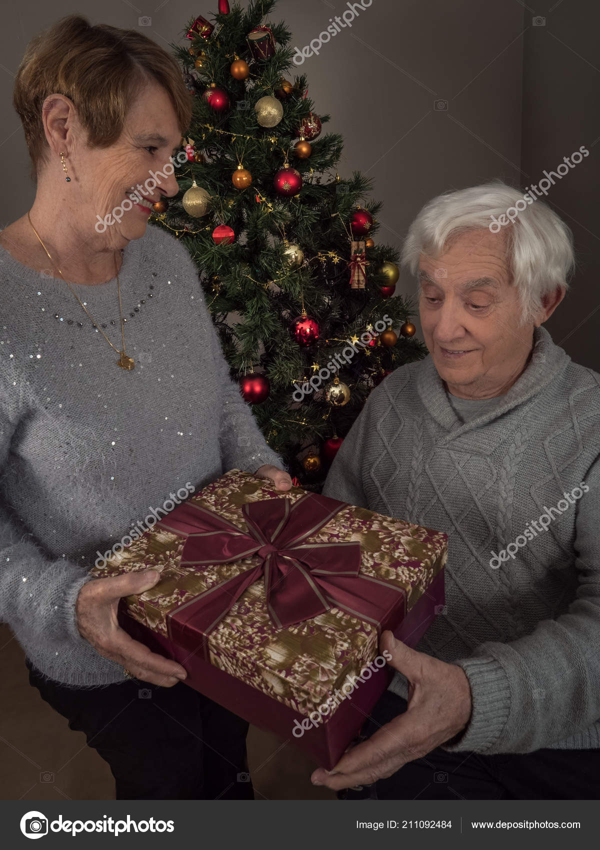 A Husband For Christmas.Vertical Portrait Elderly Woman Giving Gift Her Husband