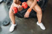 Photo cropped image of sportswoman in wristbands doing exercise with dumbbell at gym